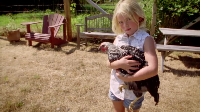 girl holding chicken in yard / looking up and smiling at camera / petting chicken - アディロンダックチェア点の映像素材/bロール
