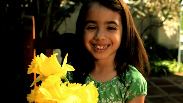 cu girl holding daffodil flowers and smiling / los angeles, california, usa - mittellanges haar stock-videos und b-roll-filmmaterial