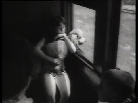 vidéos et rushes de b/w girl holding dog sitting by window on train / sound - seulement des petites filles