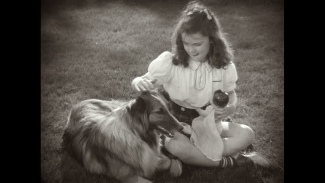 vídeos de stock, filmes e b-roll de ms girl holding doll and stroking dog while sitting on lawn / united states - 1950