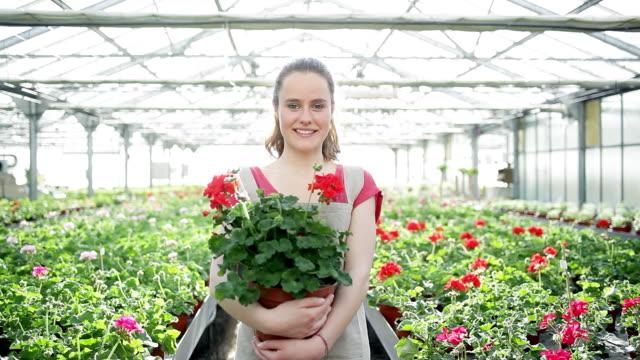 stockvideo's en b-roll-footage met ms zi girl holding flowers pot and standing in green house / albi, midi-pyrennees, france - alleen één tienermeisje