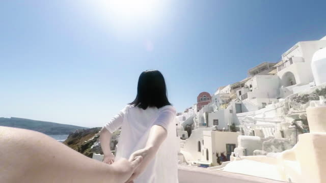 slo girl holding hands with boy and runing on santorini, greece - insel santorin stock-videos und b-roll-filmmaterial