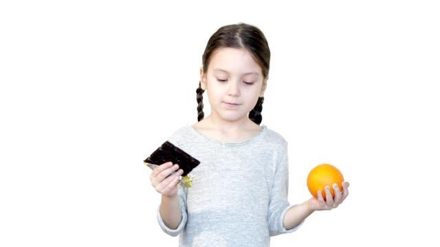 mädchen hält orange und schokolade. sie muss sich für eine entscheiden. - wahlmöglichkeit stock-videos und b-roll-filmmaterial
