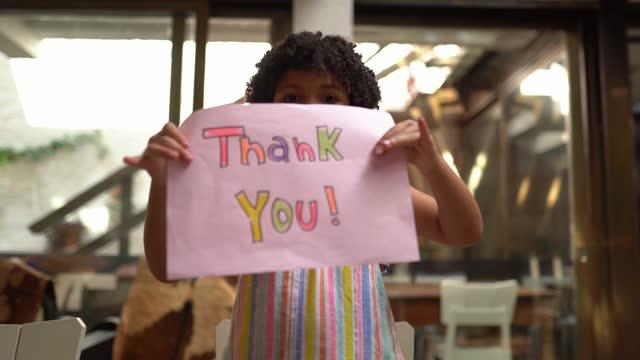 vídeos y material grabado en eventos de stock de chica sosteniendo papel con 'gracias' escrito en casa - punto de vista webcam - señal mensaje