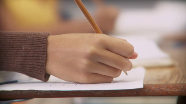 ecu, girl (14-15) holding pencil over test sheet, richmond, virginia, usa - 試験点の映像素材/bロール