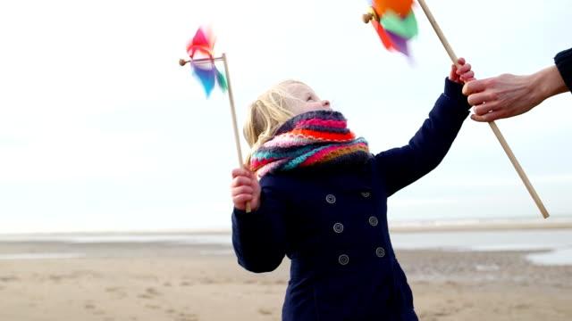 ms ragazza holding pinwheel e giocando sulla spiaggia - girandola video stock e b–roll