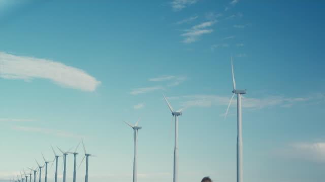 ws td girl holding pinwheel staring at wind turbines / zillah, washington, usa   - girandola video stock e b–roll