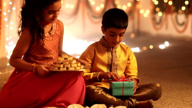 MS Girl holding plate of sweet and feeding to her brother, boy holding gift box in diwali festival