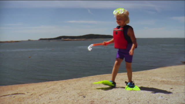 SM WS Girl holding snorkel and walking in wet suit and flippers along beach near sea / Vinalhaven, Maine, USA
