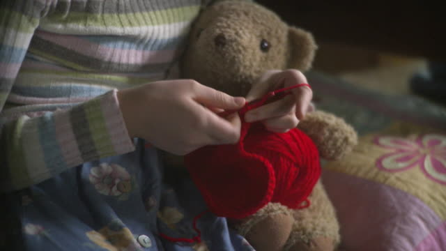 ms tu td girl (10-11) holding teddy bear and crocheting heart / newark, illinois, usa - テディベア点の映像素材/bロール