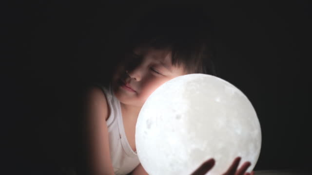 vídeos de stock, filmes e b-roll de garota segurando a lua à noite - sonhar acordado