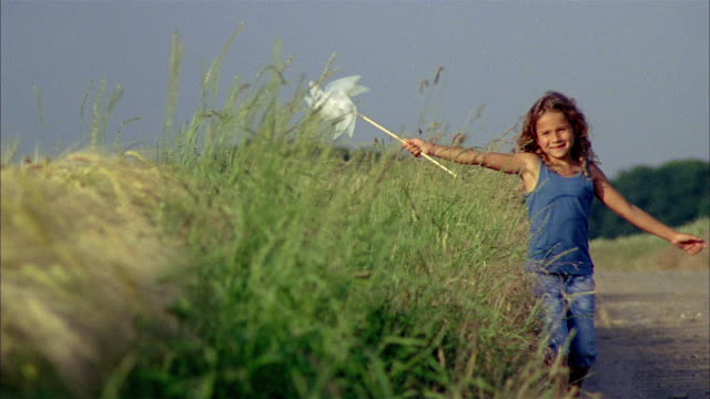 ws tu r/f slo mo girl (6-7) holding toy windmill and running through field / brussels, brabant, belgium - nur mädchen stock-videos und b-roll-filmmaterial