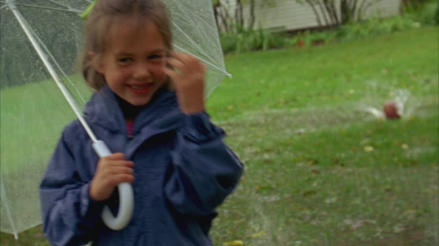 vidéos et rushes de ms, shaky, girl (6-7) holding umbrella smiling to camera then playing with boy (6-7) in flooded field, yarmouth, maine, usa - vêtement de pluie
