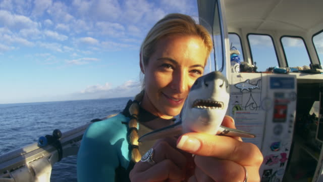A girl holds a small plastic shark up to camera