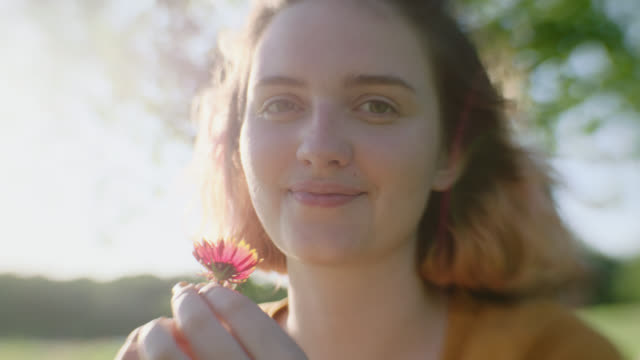 CU SLO MO. Girl holds flower in hand and smiles at camera in sunny meadow.