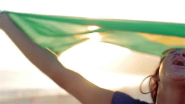 girl holds up brazilian flag in the wind and cheers on ipanema beach at sunset - 振る点の映像素材/bロール