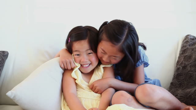 Girl hugging her sister as they sit together