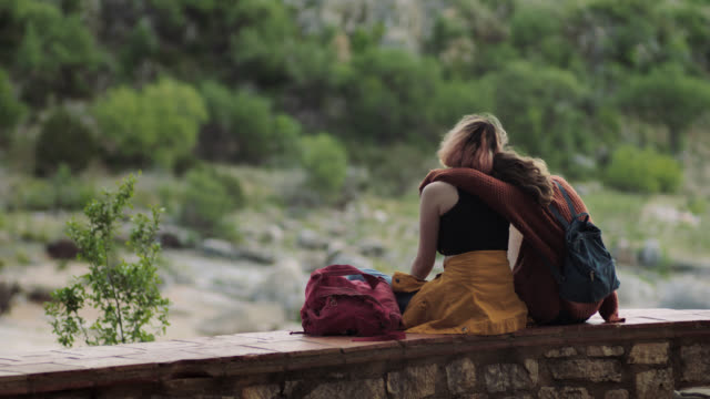 vídeos de stock e filmes b-roll de girl hugs and leans on sister as they look out from scenic overlook in pedernales falls state park. - abraçar