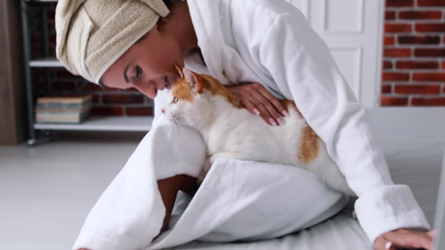 a girl in a bathrobe enjoys with her cat. she caresses and kisses her. - bathrobe stock videos & royalty-free footage
