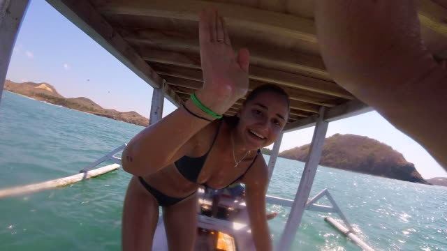 A girl in a bikini gives a high five and fist bump on a boat. - Slow Motion