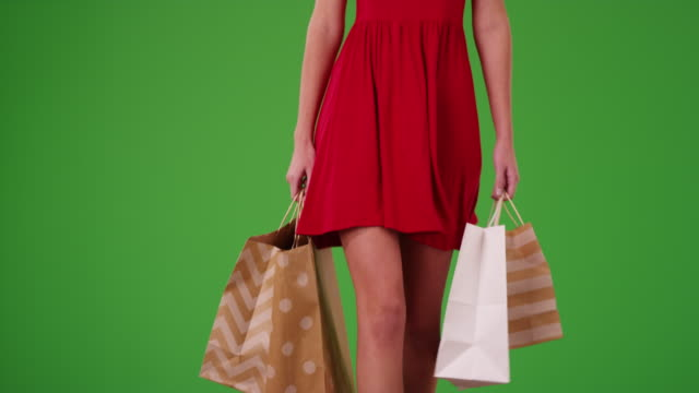 girl in a dress who just went shopping walking toward the camera on green screen - menschliches gelenk stock-videos und b-roll-filmmaterial