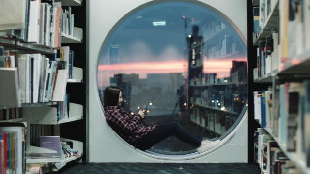 girl in a library using her smart phone - endast en tonårsflicka bildbanksvideor och videomaterial från bakom kulisserna