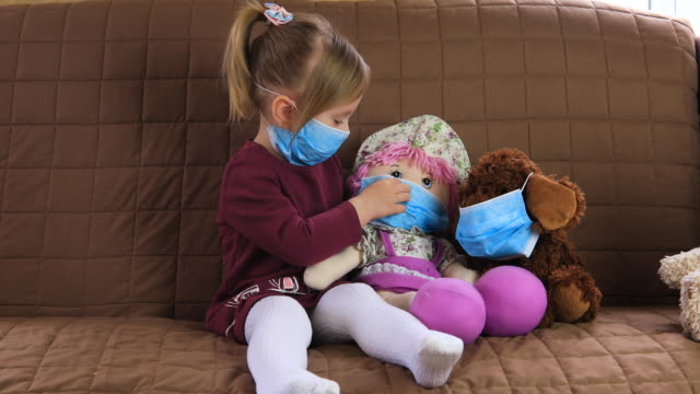 girl in a medical mask playing doctor with her toys. - doll stock videos & royalty-free footage