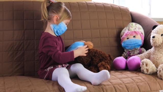 vídeos y material grabado en eventos de stock de girl in a medical mask playing doctor with her toys. - juguete