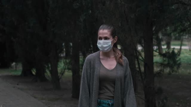 vídeos y material grabado en eventos de stock de girl in a protective medical mask walks in the park. - neumonía