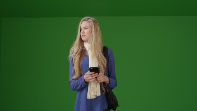 vídeos de stock e filmes b-roll de girl in a scarf uses her smart phone while she waits on green screen - liso