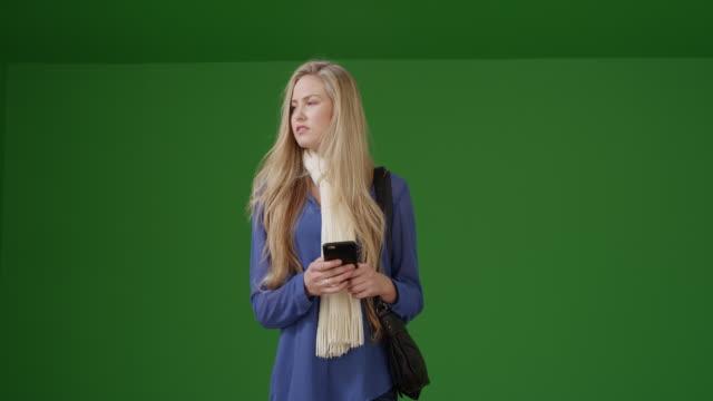 vídeos y material grabado en eventos de stock de girl in a scarf uses her smart phone while she waits on green screen - liso