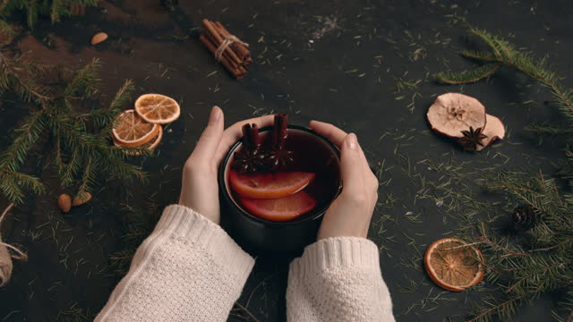 vídeos de stock e filmes b-roll de a girl in a soft knitted sweater holds a cup of mulled wine with both hands - bebida quente