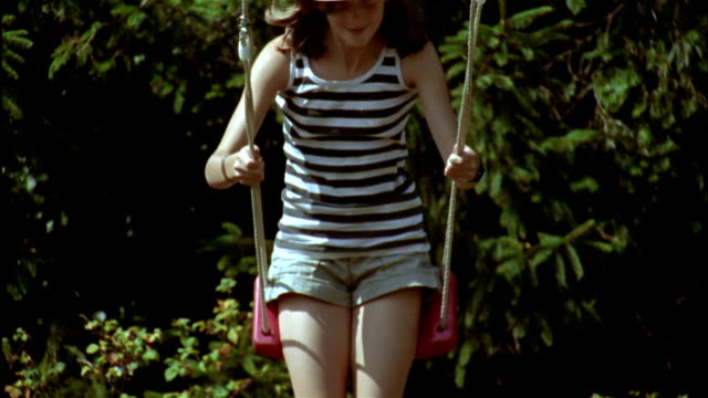 a girl in a straw cowboy hat swings on a swing in a garden. - cowboy hat stock videos & royalty-free footage