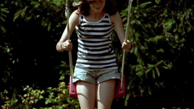 a girl in a straw cowboy hat swings on a swing in a garden. - straw hat stock videos & royalty-free footage