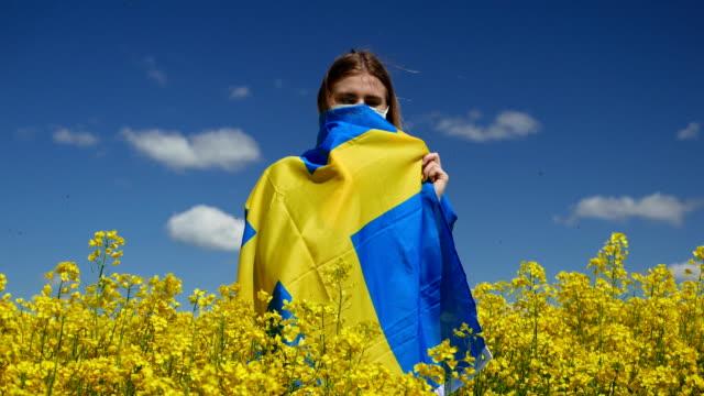 mädchen in einer chirurgischen maske auf einem schönen rapsfeld mit der flagge von schweden - sweden stock-videos und b-roll-filmmaterial