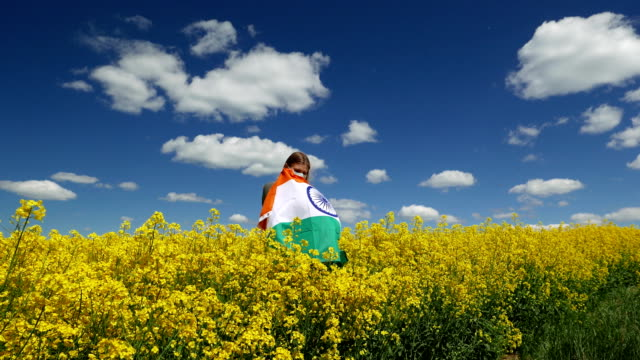 girl in a surgical mask on a beautiful rapeseed field with the flag of india - india politics stock videos & royalty-free footage
