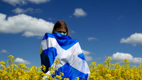 girl in a surgical mask on a beautiful rapeseed field with the flag of scotland - government stock videos & royalty-free footage