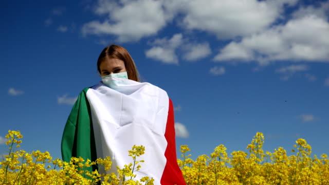ragazza in maschera chirurgica su un bellissimo campo di colza con la bandiera d'italia - bandiera video stock e b–roll