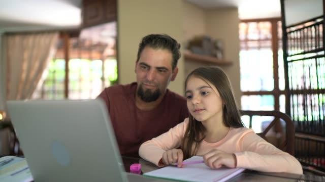 vídeos de stock, filmes e b-roll de menina em uma aula virtual com apoio do pai - distante