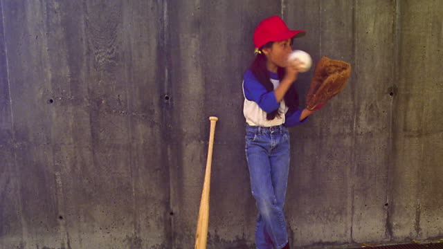 stockvideo's en b-roll-footage met girl in baseball hat leaning on wall throwing softball in to baseball glove / next to wooden bat - honkbal teamsport