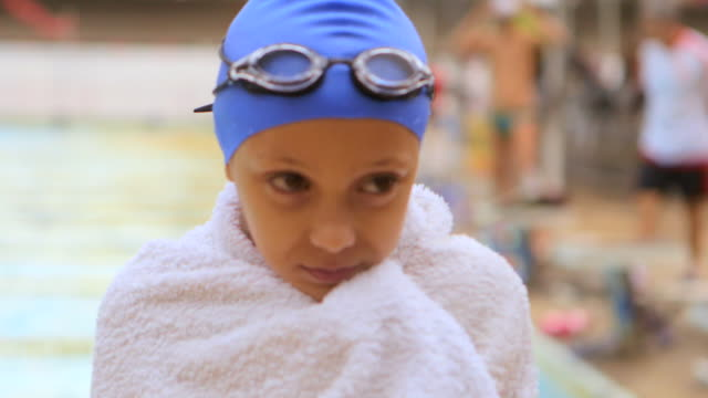 vidéos et rushes de close up handheld girl in bathing cap swimming goggles and towel smiles at camera poolside outdoors - une seule petite fille