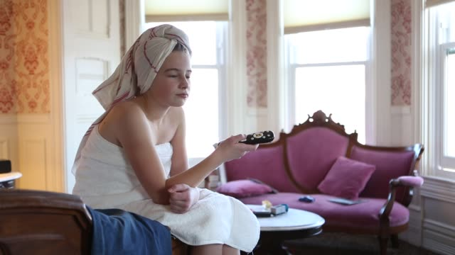 stockvideo's en b-roll-footage met girl in bathrobe with tv remote - badjas