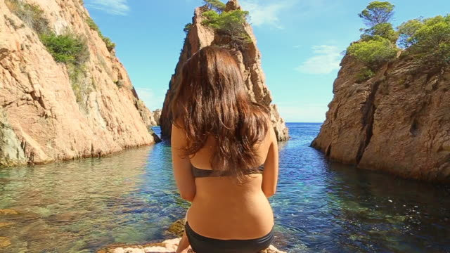 Girl in bikini posing like a model with his back and long hair with a stunning Costa Brava landscape in the beach during summer time.