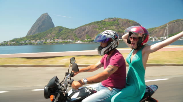 Girl in blue dress cheers and throws hands in the air as mototaxi speeds by beautiful Guanabara Bay