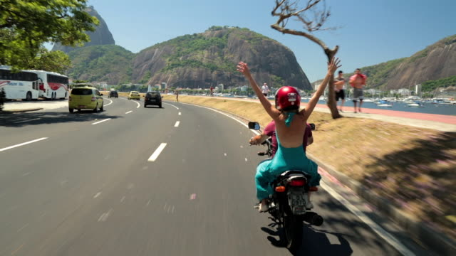Girl in blue dress throws hands in the air as mototaxi speeds by beautiful Guanabara Bay