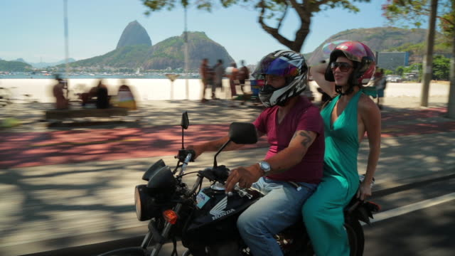 girl in blue dress throws head back and laughs on mototaxi ride through rio - sports event stock videos & royalty-free footage