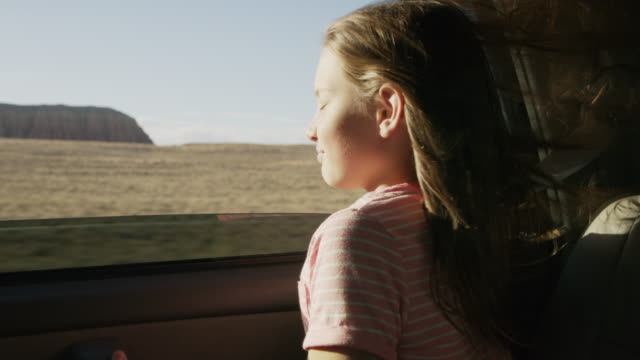 girl in car leaning out car window enjoying wind blowing hair / hanksville, utah, united states - leaning stock videos & royalty-free footage