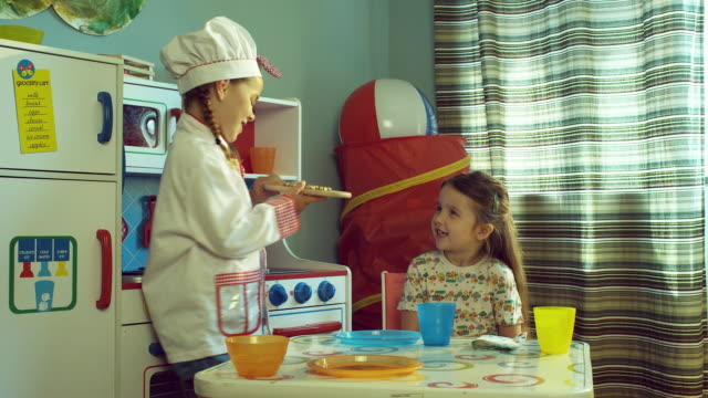 ms girl (4-5) in chef outfit serves cookies to another girl in play kitchen set / burbank, california, usa - 一人前の量点の映像素材/bロール