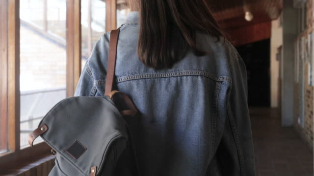 vidéos et rushes de girl in denim jacket walks to class, tracking shot - université