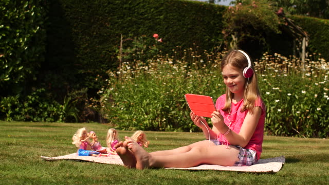 girl in garden playing ipad digital tablet - little girls bare feet stock videos and b-roll footage